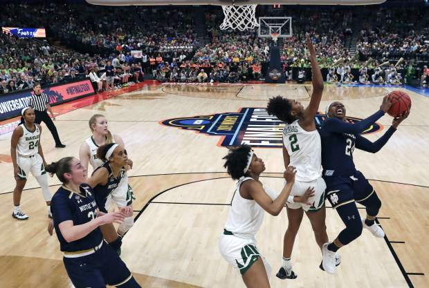 Notre Dame's Arike Ogunbowale, right, goes up for a shot against Baylor's DiDi Richards (2) during the first half of the Final Four championship game of the NCAA women's college basketball tournament Sunday, April 7, 2019, in Tampa, Fla. (AP Photo/John Raoux)