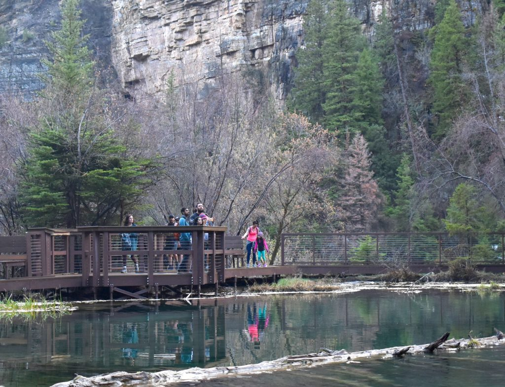 Visitors admire Bridal Falls, where Dead Horse Creek flows into Hanging Lake.