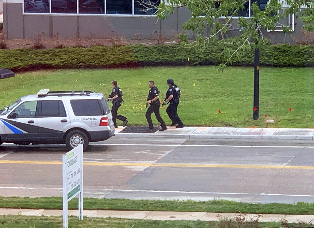 Armed police officers and others are seen outside STEM School Highlands Ranch, a charter middle school in the Denver suburb of Highlands Ranch, Colo., after a shooting Tuesday, May 7, 2019. Authorities said several people were injured and a few suspects were in custody. (Courtney Harper via AP)