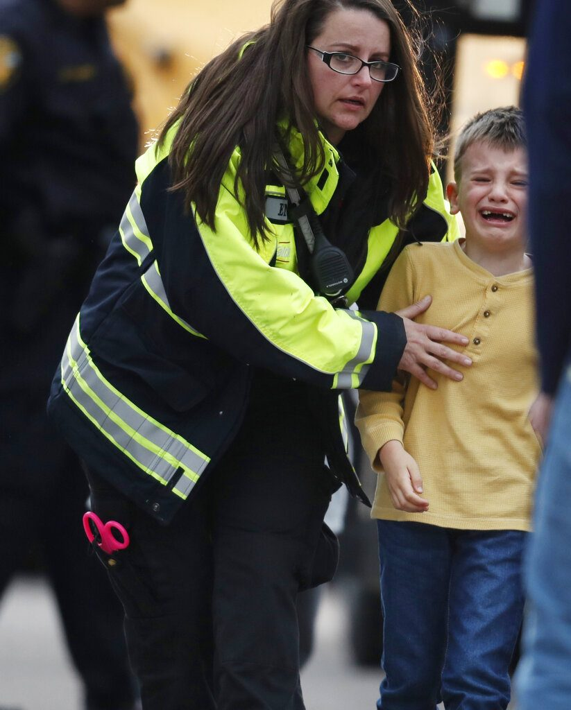 A young boy is led from a bus to a recreation center where students were reunited with their parents after a shooting at a suburban Denver middle school Tuesday, May 7, 2019, in Highlands Ranch, Colo. (AP Photo/David Zalubowski)