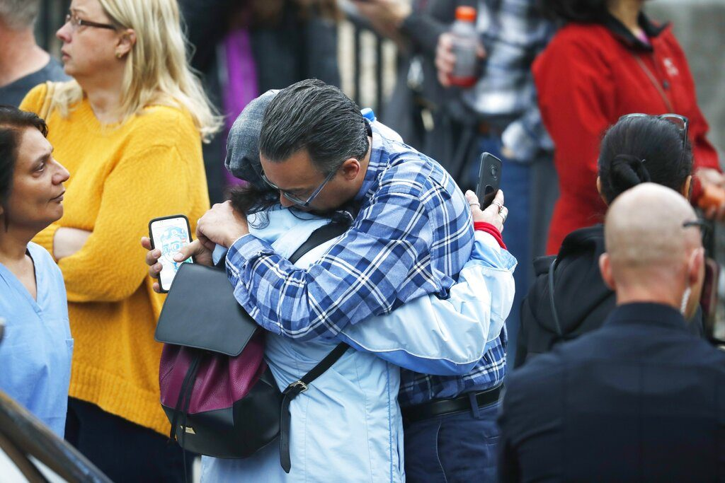 Parents hug as they wait for the arrival of their children at the recreation center where the students were reunited with their parents Tuesday, May 7, 2019, in Highlands Ranch, Colo. (AP Photo/David Zalubowski)
