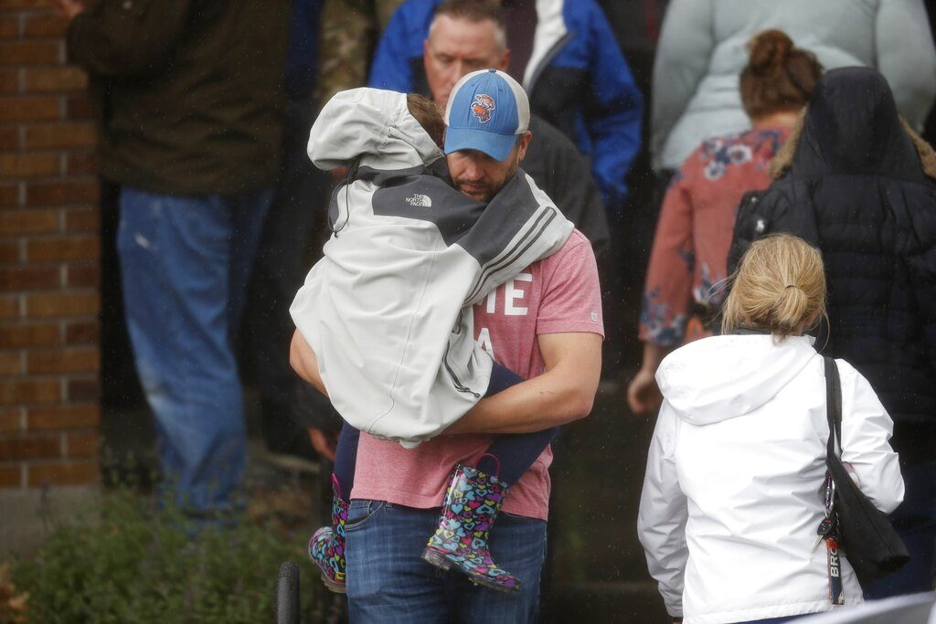 A man carries a child out of a recreation center set up for students to get reunited with their parents after a shooting at a suburban Denver middle school Tuesday, May 7, 2019, in Highlands Ranch, Colo. (AP Photo/David Zalubowski)