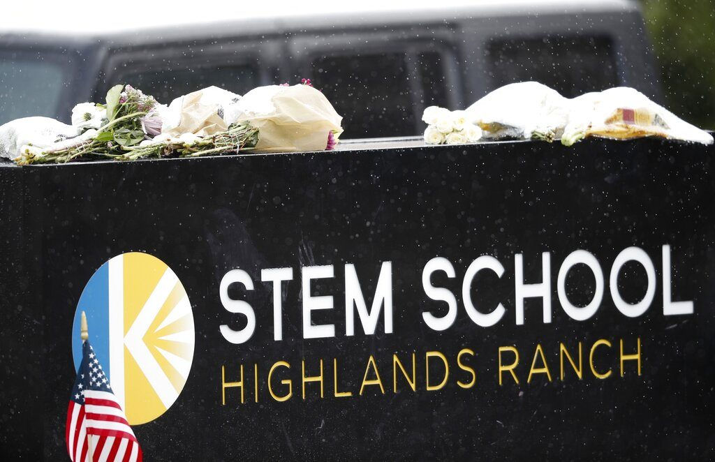 A light snow covers bouquets of flowers placed on the sign for STEM School Highlands Ranch following Tuesday's shooting, in Highlands Ranch, Colo., Thursday, May 9, 2019.  (AP Photo/David Zalubowski)