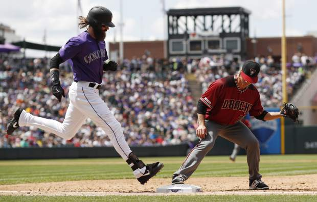 Arizona Diamondbacks starting pitcher Zack Greinke, right, fields the throw at first to put out Colorado Rockies' Charlie Blackmon after he hit a ground ball to Arizona first baseman Christian Walker in the third inning of a baseball game Sunday, May 5, 2019, in Denver. (AP Photo/David Zalubowski)