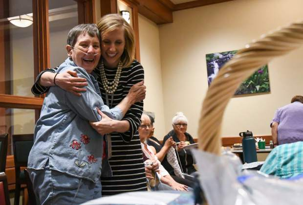 Kati Ledall embraces Threads of Love volunteer Judy Elzinga during their weekly get together at Valley View Hospital.
