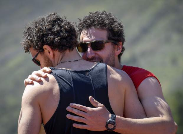 Nancy Reinisch's sons Marco and Chas Salmen share an embrace after finishing heat 1 of the Mother's Day Mile Sunday in Glenwood Springs.