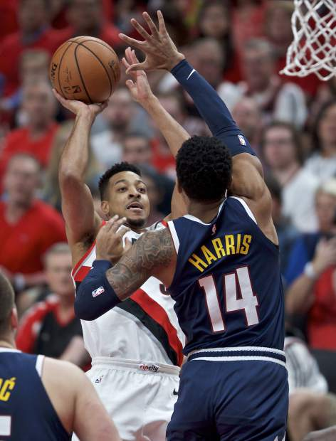 Portland Trail Blazers guard CJ McCollum, left, shoots over Denver Nuggets guard Gary Harris during the first half of Game 4 of an NBA basketball second-round playoff series Sunday, May 5, 2019, in Portland, Ore. (AP Photo/Craig Mitchelldyer)