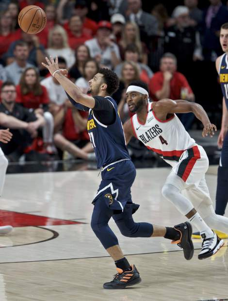 Denver Nuggets guard Jamal Murray, left, collects the ball in front of Portland Trail Blazers forward Maurice Harkless during the first half of Game 4 of an NBA basketball second-round playoff series Sunday, May 5, 2019, in Portland, Ore. (AP Photo/Craig Mitchelldyer)