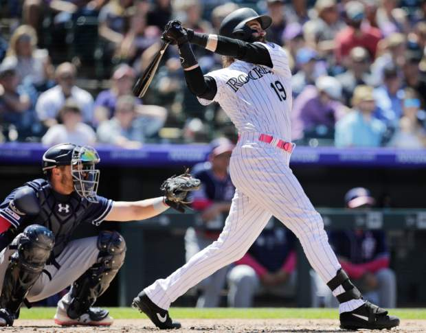 Colorado Rockies' Charlie Blackmon (19) hits a home run in the fourth inning of a baseball game as San Diego Padres catcher Austin Allen, left, looks on in Denver, Sunday, May 12, 2019. (AP Photo/Joe Mahoney)