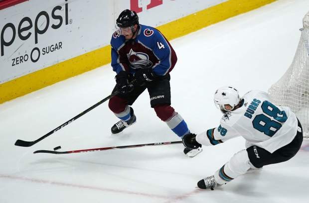 San Jose Sharks defenseman Brent Burns, right, knocks the puck away from Colorado Avalanche defenseman Tyson Barrie in the first period of Game 6 of an NHL hockey second-round playoff series Monday, May 6, 2019, in Denver. (AP Photo/Jack Dempsey)
