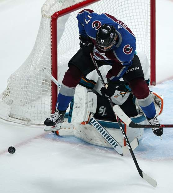 Colorado Avalanche center Tyson Jost, front, tries to redirect the puck toward San Jose Sharks goaltender Martin Jones in the first period of Game 6 of an NHL hockey second-round playoff series Monday, May 6, 2019, in Denver. (AP Photo/Jack Dempsey)