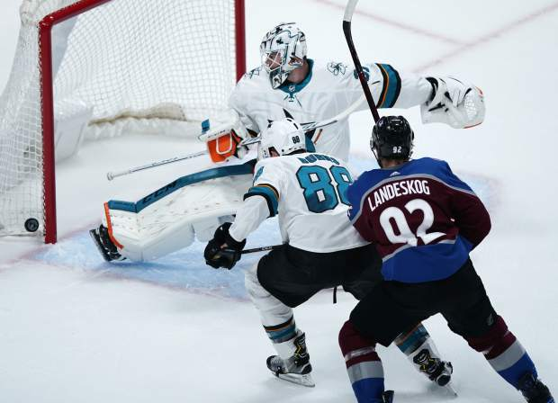 San Jose Sharks goaltender Martin Jones, back, makes a kick-save of a shot as defenseman Brent Burns, center, and Colorado Avalanche left wing Gabriel Landeskog pursue the puck in the first period of Game 6 of an NHL hockey second-round playoff series Monday, May 6, 2019, in Denver. (AP Photo/Jack Dempsey)