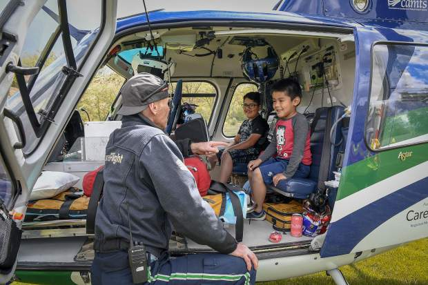 Rob Klimek, Care Flight parmedic, shows Henry Colmenares, 8, and his brother Kevin, 5, both of Silt around the the Care Flight helicopter Saturday during GARCO First Responders Day at Stoney Ridge Park.
