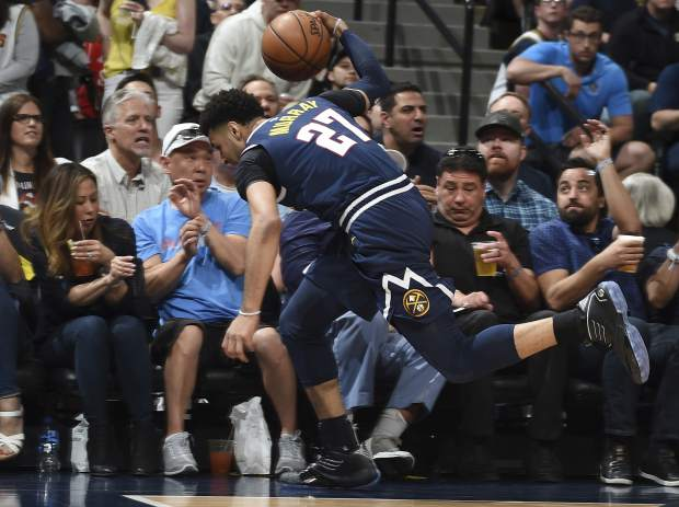Denver Nuggets guard Jamal Murray dives into the fans in the courtside seats to save a loose ball in the first half of Game 7 of an NBA basketball second-round playoff series against the Portland Trail Blazers Sunday, May 12, 2019, in Denver. (AP Photo/John Leyba)