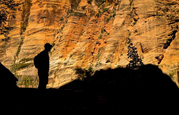 A hiker stops and looks around whiel hiking the Angel's Landing trail in Zion National Park during an early morning hike.