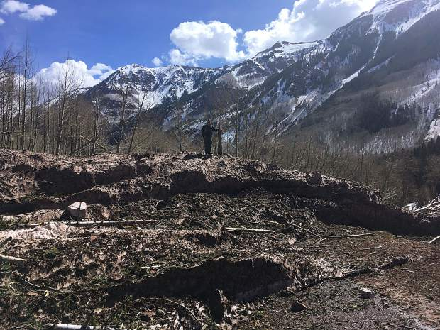 A man stands on the top of avalanche debris covering Maroon Creek Road in mid-April.