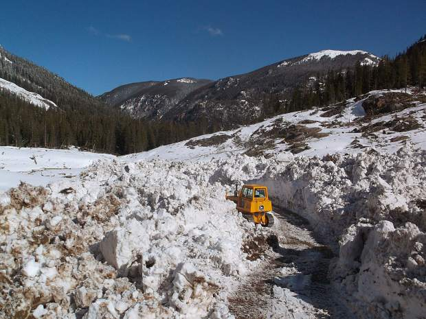 Glenn Schryver's bulldozer is dwarfed by the snowfield along Lincoln Creek Road. Bashing through tree trunks and boulders forced emergency repairs on the machine.