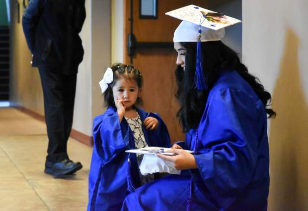 Paula Montoya and her 1-year-old daughter Samara Reyes prepare for the Yampah Mountain HIgh School graduation held in Carbondale on Friday morning.