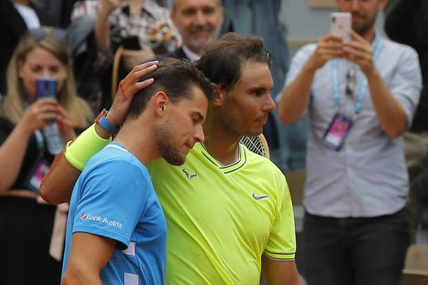 Spain's Rafael Nadal, right, hugs Austria's Dominic Thiem, left, after celebrating his record 12th French Open tennis tournament title after winning his men's final match in four sets, 6-3, 5-7, 6-1, 6-1, at the Roland Garros stadium in Paris, Sunday, June 9, 2019. (AP Photo/Michel Euler)