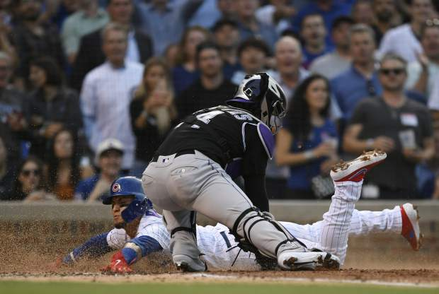 Chicago Cubs' Javier Baez slides into home plate safely on a Carlos Gonzalez double as Colorado Rockies catcher Tony Wolters attempts to apply the tag during the second inning of a baseball game Tuesday, June 4, 2019, in Chicago. (AP Photo/Paul Beaty)