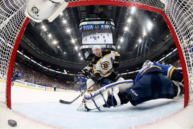 Boston Bruins center Charlie Coyle (13) scores a goal against St. Louis Blues goaltender Jordan Binnington, right, during the first period in Game 4 of the NHL hockey Stanley Cup Final Monday, June 3, 2019, in St. Louis. (Bruce Bennett/Pool via AP)