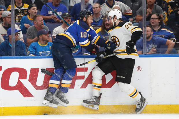 St. Louis Blues center Brayden Schenn (10) and Boston Bruins defenseman Brandon Carlo (25) battle for the puck during the second period of Game 4 of the NHL hockey Stanley Cup Final Monday, June 3, 2019, in St. Louis. The Blues won 4-2 to even the series 2-2. (AP Photo/Jeff Roberson)