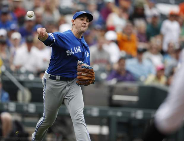 Toronto Blue Jays starting pitcher Aaron Sanchez throws to first base to put out Colorado Rockies' Raimel Tapia to end the sixth inning of a baseball game Sunday, June 2, 2019, in Denver. (AP Photo/David Zalubowski)