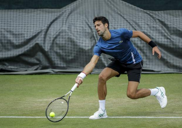 Serbia's Novak Djokovic plays a practice session ahead of the Wimbledon Tennis Championships in London Sunday, June 30, 2019. (AP Photo/Ben Curtis)