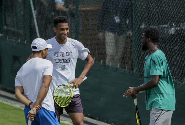 Canada's Felix Auger-Aliassime, left, and United States's Frances Tiafoe, right, laugh during a break at a practice session ahead of the Wimbledon Tennis Championships in London Sunday, June 30, 2019. (AP Photo/Ben Curtis)
