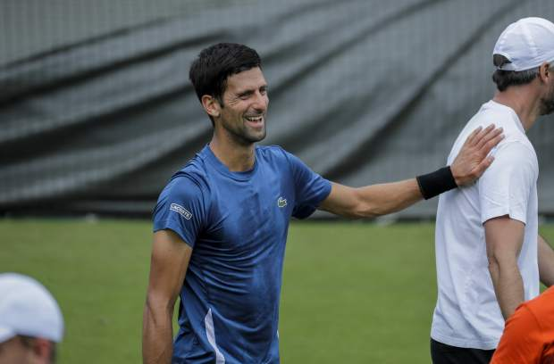 Serbia's Novak Djokovic laughs during a practice session ahead of the Wimbledon Tennis Championships in London Sunday, June 30, 2019. (AP Photo/Ben Curtis)