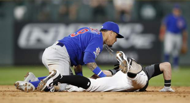 Chicago Cubs shortstop Javier Baez, left, tags out Colorado Rockies' Ryan McMahon as he slides into second base while trying to stretch his RBI-single into a double in the eighth inning of a baseball game, Monday, June 10, 2019, in Denver. The Rockies won 6-5. (AP Photo/David Zalubowski)