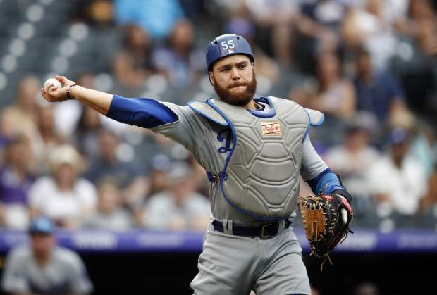 Los Angeles Dodgers catcher Russell Martin throws to first base to put out Colorado Rockies' Ian Desmond in the ninth inning of a baseball game Sunday, June 30, 2019, in Denver. (AP Photo/David Zalubowski)