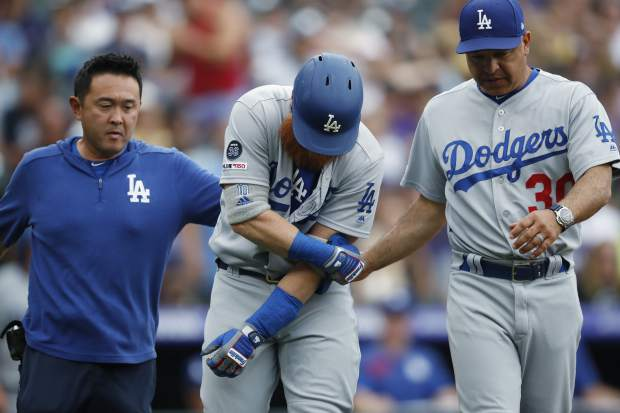 Los Angeles Dodgers pinch hitter Justin Turner, center, grabs his left arm after taking a pitch to the elbow which forced in a run against Colorado Rockies starting pitcher Chad Bettis in the sixth inning of a baseball game Sunday, June 30, 2019, in Denver. A team trainer, left, and manager Dave Roberts check on Turner. (AP Photo/David Zalubowski)