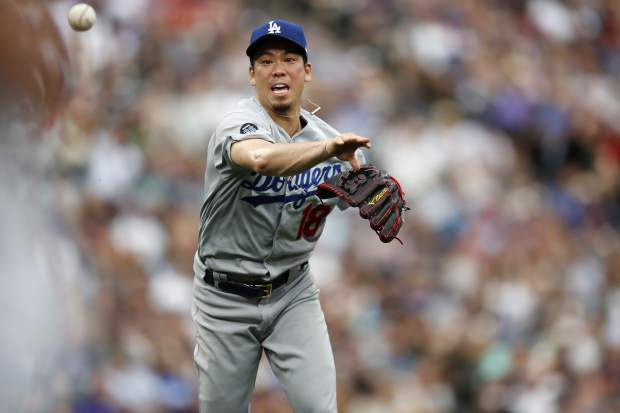 Los Angeles Dodgers starting pitcher Kenta Maeda throws to first base to put out Colorado Rockies' David Dahl to end the third inning of a baseball game Sunday, June 30, 2019, in Denver. (AP Photo/David Zalubowski)