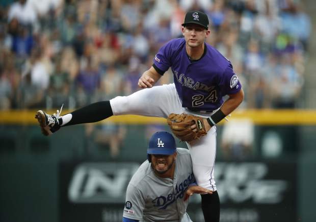 Colorado Rockies second baseman Ryan McMahon, top, jumps over Los Angeles Dodgers' Edwin Rios after forcing him out at second base on the front end of a double play hit into by Enrique Hernandez to end the top of the second inning of a baseball game Sunday, June 30, 2019, in Denver. (AP Photo/David Zalubowski)