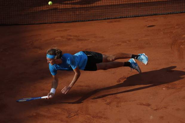 Greece's Stefanos Tsitsipas falls after diving to return a shot against Switzerland's Stan Wawrinka during their fourth round match of the French Open tennis tournament at the Roland Garros stadium in Paris, Sunday, June 2, 2019. (AP Photo/Christophe Ena)