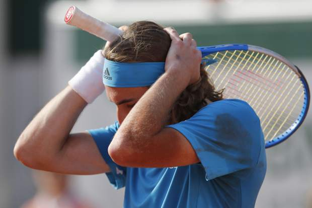 Greece's Stefanos Tsitsipas plays a shot against Switzerland's Stan Wawrinka during their fourth round match of the French Open tennis tournament at the Roland Garros stadium in Paris, Sunday, June 2, 2019. (AP Photo/Christophe Ena )