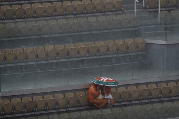 Two spectators take cover during a downpour at center court after the quarterfinal match of the French Open tennis tournament between Japan's Kei Nishikori and Spain's Rafael Nadal was interrupted at the Roland Garros stadium in Paris, Tuesday, June 4, 2019. (AP Photo/Pavel Golovkin)