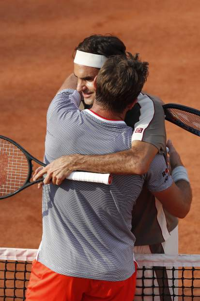 Switzerland's Roger Federer and Switzerland's Stan Wawrinka hug after their quarterfinal match of the French Open tennis tournament against which Federer won in four sets, 7-6 (7-4), 4-6, 7-6 (7-5), 6-4, at the Roland Garros stadium in Paris, Tuesday, June 4, 2019. (AP Photo/Jean-Francois Badias)