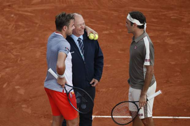 Switzerland's Roger Federer, right, and Switzerland's Stan Wawrinka, left, joke, during an interruption of their quarterfinal match of the French Open tennis tournament because of the rain at the Roland Garros stadium in Paris, Tuesday, June 4, 2019. (AP Photo/Jean-Francois Badias)