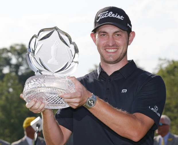 Patrick Cantlay raises the trophy after winning the Memorial golf tournament Sunday, June 2, 2019, in Dublin, Ohio. (AP Photo/Jay LaPrete)