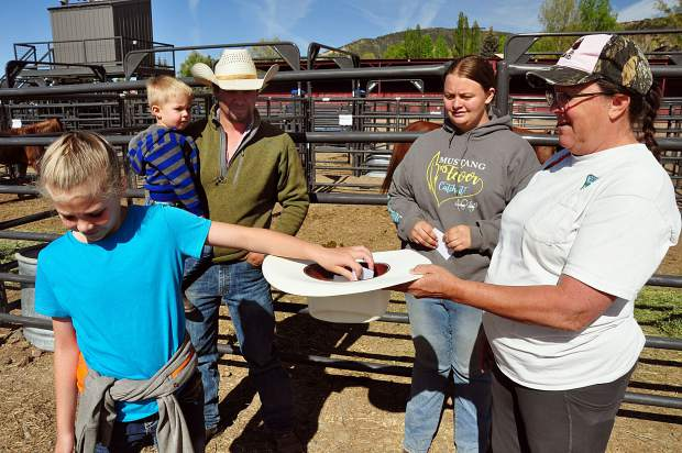 Trainers draw lots to see how gets what horse to train for the Mustang Meeker Makeover. One young girl draws her lot while Cody Rhyne, Paige Burnham and, Melissa Kindall look on.