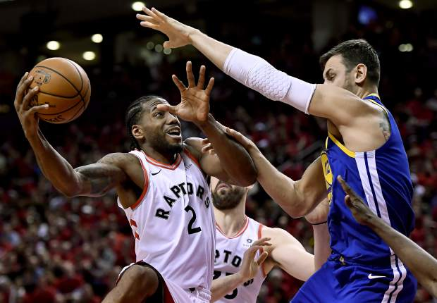 Toronto Raptors forward Kawhi Leonard (2) stretches to keep the ball from Golden State Warriors center Andrew Bogut (12) as he drives to the net during the second half of Game 2 of basketball's NBA Finals, Sunday, June 2, 2019, in Toronto. (Frank Gunn/The Canadian Press via AP)