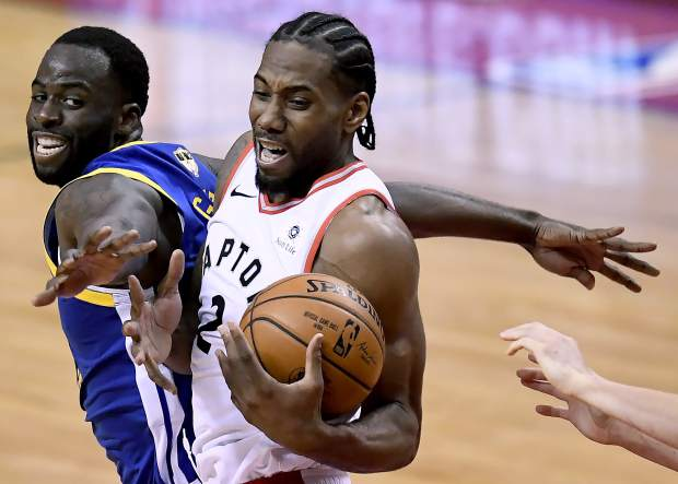 Golden State Warriors forward Draymond Green (23) tries to block Toronto Raptors forward Kawhi Leonard (2) during the second half of Game 2 of basketball's NBA Finals, Sunday, June 2, 2019, in Toronto. (Frank Gunn/The Canadian Press via AP)
