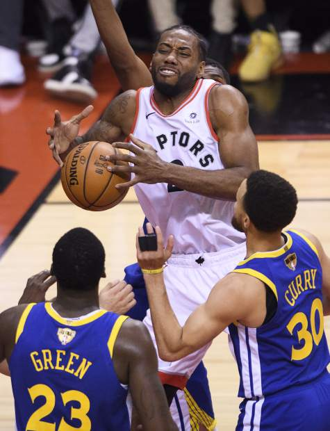 Toronto Raptors forward Kawhi Leonard (2) is fouled as Golden State Warriors forward Draymond Green (23) and guard Stephen Curry (30) look on during the first half of Game 2 of basketball's NBA Finals, Sunday, June 2, 2019, in Toronto. (Nathan Denette/The Canadian Press via AP)