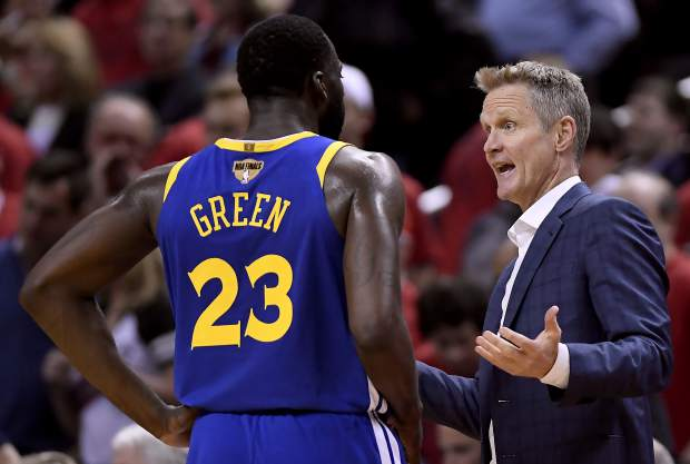 Golden State Warriors forward Draymond Green (23) and head coach Steve Kerr confer courtside during the first half of Game 2 of basketball's NBA Finals against the Toronto Raptors, Sunday, June 2, 2019, in Toronto. (Frank Gunn/The Canadian Press via AP)