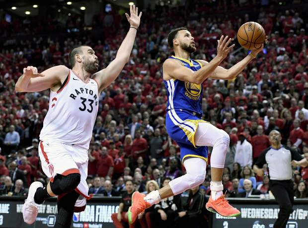 Golden State Warriors guard Stephen Curry (30) drives to the net as Toronto Raptors center Marc Gasol (33) looks on during the first half of Game 2 of basketball's NBA Finals, Sunday, June 2, 2019, in Toronto. (Frank Gunn/The Canadian Press via AP)