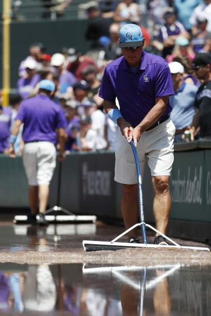 Mark Razum pushes water along the right-field stands after water discharged onto the field to create a lake in the first inning of a baseball game between the San Diego Padres and the Colorado Rockies, Sunday, June 16, 2019, in Denver. (AP Photo/David Zalubowski)