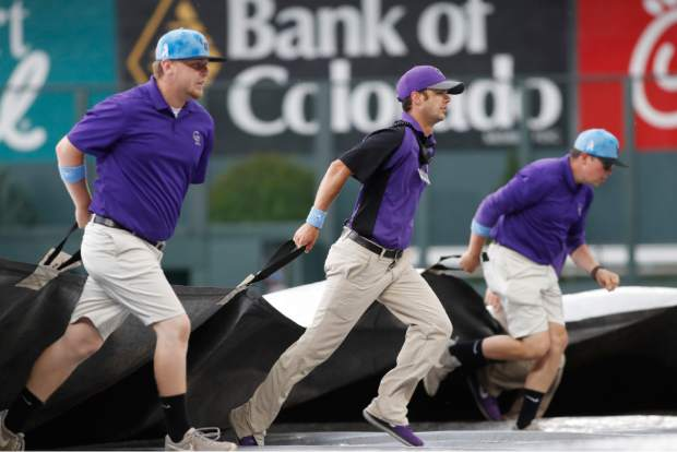 Grounds crew members pull the tarpaulin during a lightning and rain delay in the sixth inning of a baseball game between the San Diego Padres and the Colorado Rockies, Sunday, June 16, 2019, in Denver. (AP Photo/David Zalubowski)
