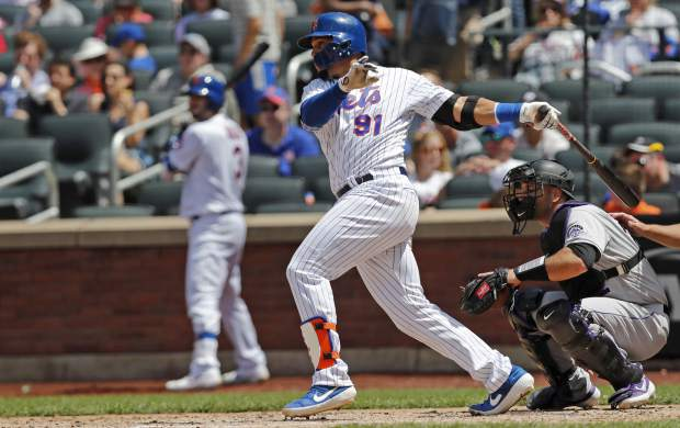 New York Mets Carlos Gomez (91) hits an RBI single during the fourth inning of a baseball game against the Colorado Rockies, Sunday, June 9, 2019, in New York. (AP Photo/Kathy Willens)